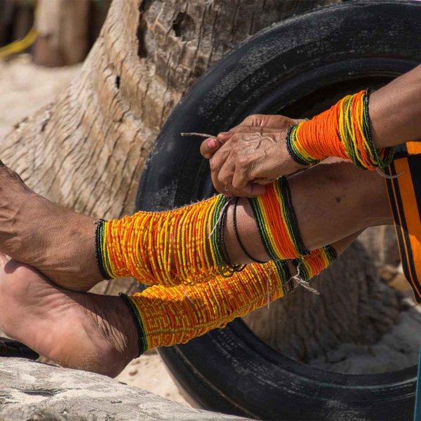 11A Kuna women putting on her beaded bracelets in San Blas, Panama